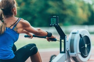 rowing machine workout in outdoors by mascular woman