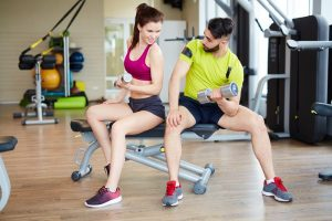 young man and woman working out at the gym