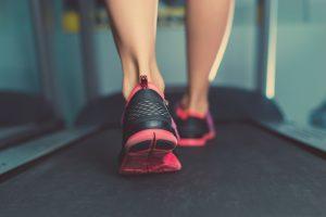 two feet walking on the treadmill belt