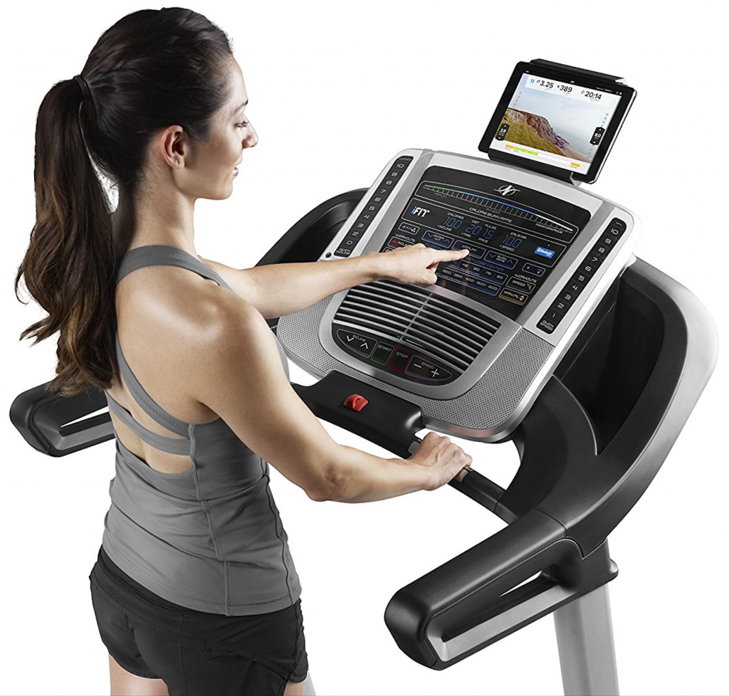 woman operating display console and buttons of NordicTrack C 700 treadmill