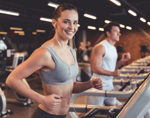 woman working out on treadmill within gym