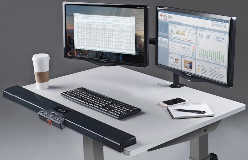 LifeSpan TR1200-DT5 Treadmill Desk having two LEDs coffee phone and writing pad with pen on the desk