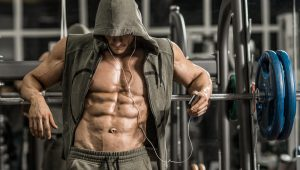 guy bodybuilder tired in gym and listen music with headset
