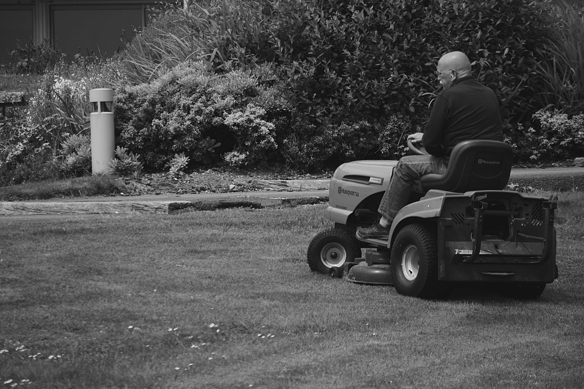 Old man using his ride-on mower to cut grass in his garden